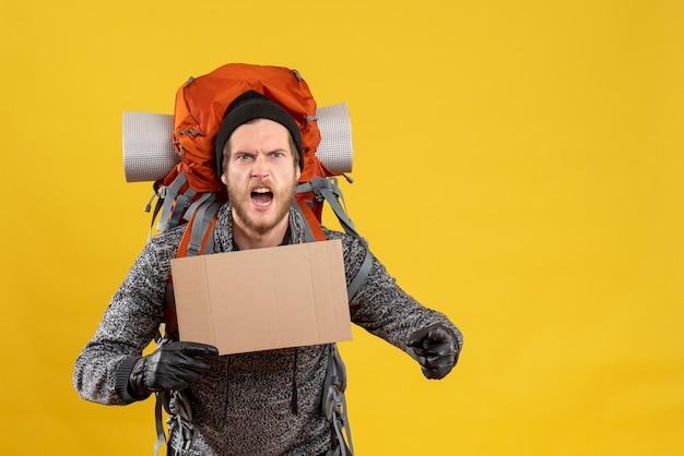 Vue de face de l'auto-stoppeur mâle en colère avec des gants en cuir et sac à dos tenant un carton vierge