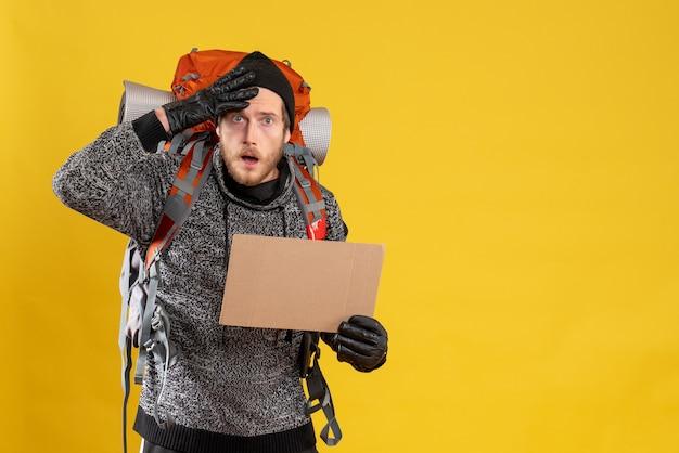 Vue de face de l'auto-stoppeur masculin agité avec des gants en cuir et sac à dos tenant du carton vierge