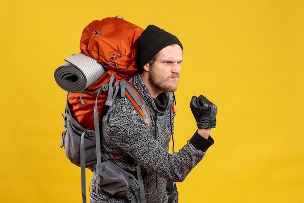 Vue de face de l'auto-stoppeur masculin en colère avec des gants en cuir et sac à dos étant prêt à se battre