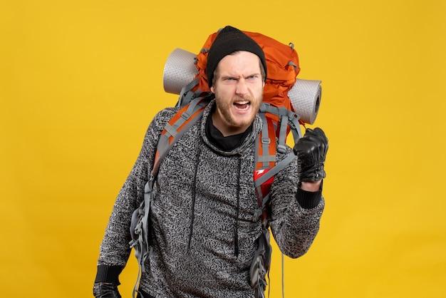 Vue de face de l'auto-stoppeur masculin en colère avec des gants en cuir et sac à dos montrant punch