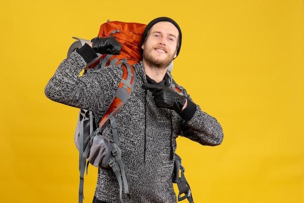 Vue de face de l'auto-stoppeur masculin confiant avec des gants en cuir et sac à dos montrant les muscles du bras