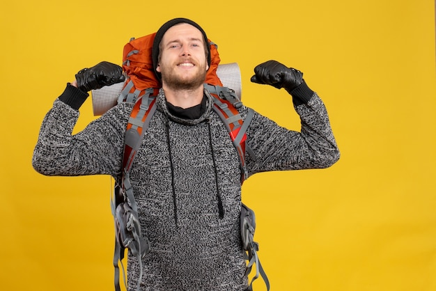Vue de face de l'auto-stoppeur masculin confiant avec des gants en cuir et sac à dos rouge montrant les muscles du bras