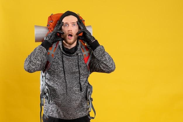 Vue de face de l'auto-stoppeur masculin déconcerté avec des gants en cuir et sac à dos à l'avant