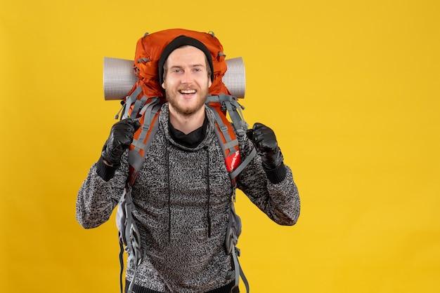Vue de face de l'auto-stoppeur masculin heureux avec des gants en cuir et sac à dos exprimant ses sentiments