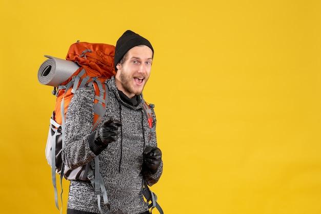 Vue de face de l'auto-stoppeur masculin heureux avec des gants en cuir et sac à dos pointant vers l'avant