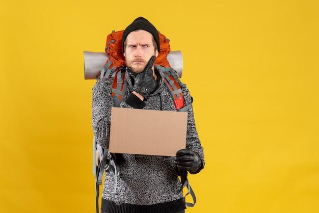 Vue de face de l'auto-stoppeur masculin intéressé avec sac à dos rouge tenant carton vierge