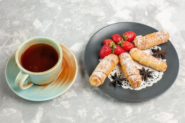 Vue de face de bagels en poudre de sucre avec des fraises et une tasse de thé