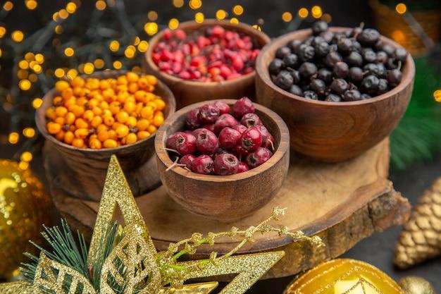 Vue de face de baies fraîches sur fond sombre photo couleur de fruits goût frais moelleux sauvage beaucoup de noël