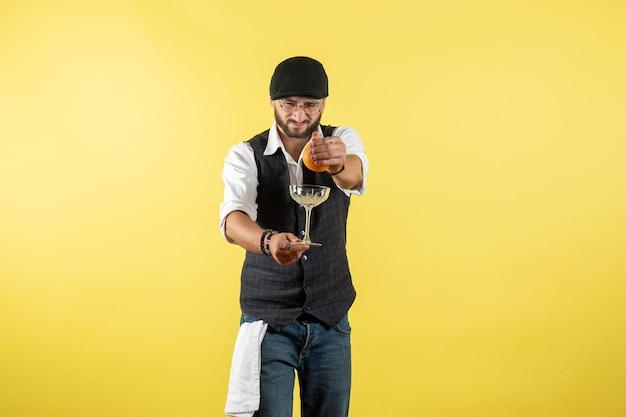 Vue de face barman mâle serrant orange sur mur jaune nuit modèle travail boisson travail club mâle