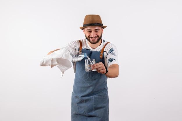 Vue de face barman mâle versant de l'eau sur le mur blanc night job club alcool boissons barre de couleur