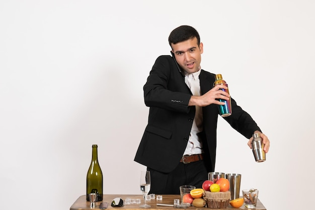 Vue de face barman masculin en costume classique faisant un verre et parlant au téléphone sur un mur blanc club d'alcool masculin boisson bar nuit