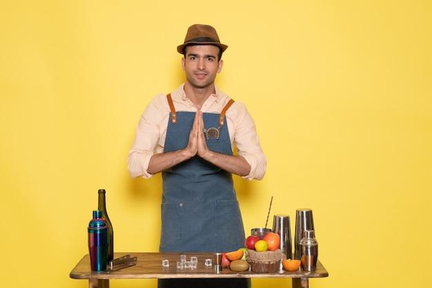 Vue de face barman masculin debout devant le bureau avec des boissons et de la glace sur le mur jaune club bar danse masculine boisson alcool de nuit