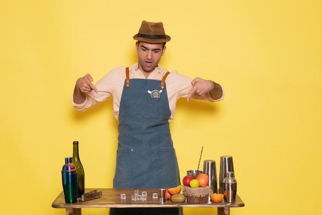 Vue de face barman masculin debout devant le bureau avec des boissons et de la glace sur un mur jaune night club bar boisson masculine