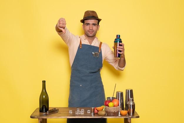 Vue de face barman masculin debout devant le bureau avec des boissons et de la glace sur un mur jaune night club bar à boissons pour hommes