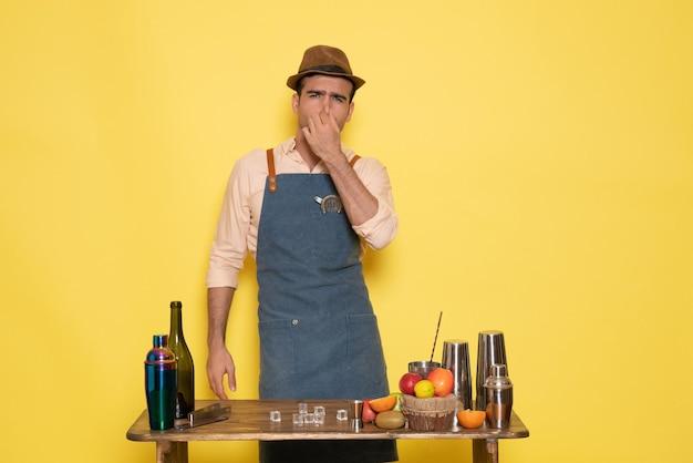 Vue de face barman masculin devant le bureau avec des boissons et des fruits sur un mur jaune boisson bar night club jus