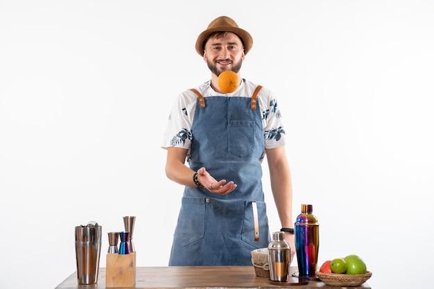 Vue de face barman masculin devant le bureau du bar jouant avec des fruits sur un sol blanc bar alcool travail de nuit club de boissons aux fruits