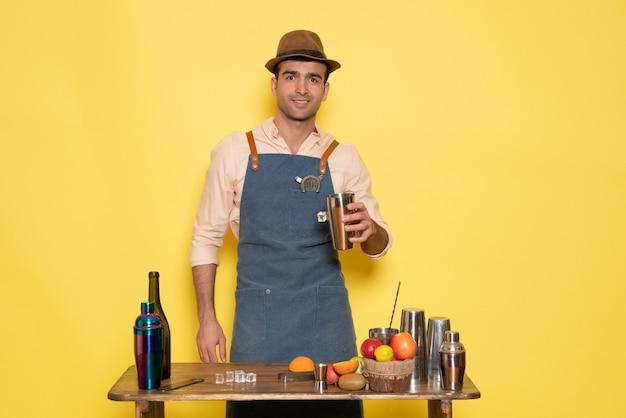 Vue de face barman masculin devant le bureau avec shakers et bouteilles faisant un verre sur un mur jaune club bar boire de l'alcool de nuit