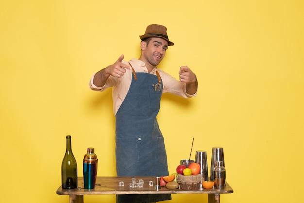 Vue de face barman masculin devant la table avec des boissons et des shakers sur un bureau jaune nuit alcool club masculin boisson bar