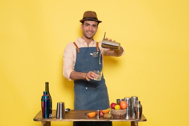 Vue de face barman masculin devant la table avec des shakers et des bouteilles faisant un verre sur un bureau jaune club bar boire de l'alcool de nuit
