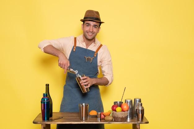 Vue de face barman masculin devant la table avec des shakers et des bouteilles faisant un verre sur un mur jaune club bar boire de l'alcool de nuit