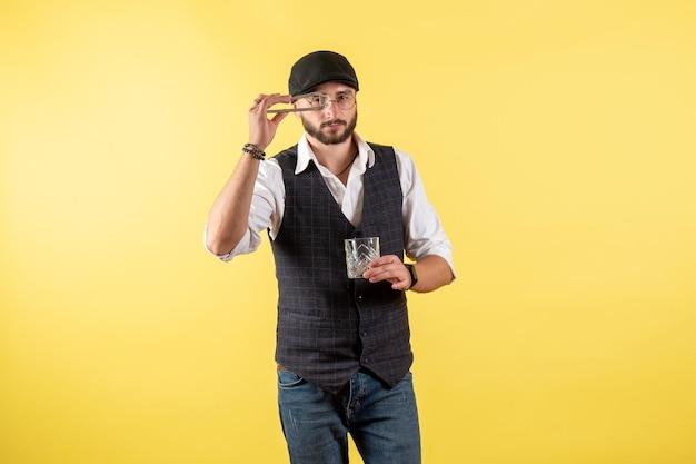 Vue de face barman masculin faisant un verre avec des glaçons sur un mur jaune boire de l'alcool travail nuit bar club masculin