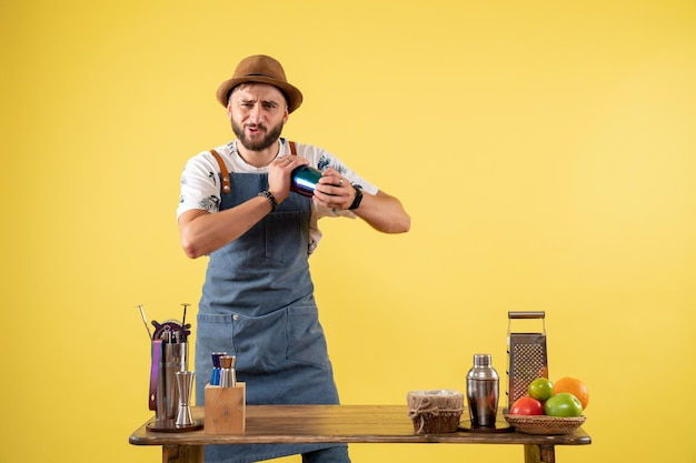 Vue de face barman masculin préparant un verre sur le mur jaune club de nuit bar de nuit boisson alcool couleur travail