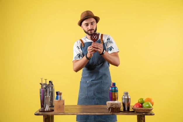 Vue de face barman masculin tenant un casse-noisette sur un mur jaune club de nuit bar de nuit boisson alcoolisée couleur de travail
