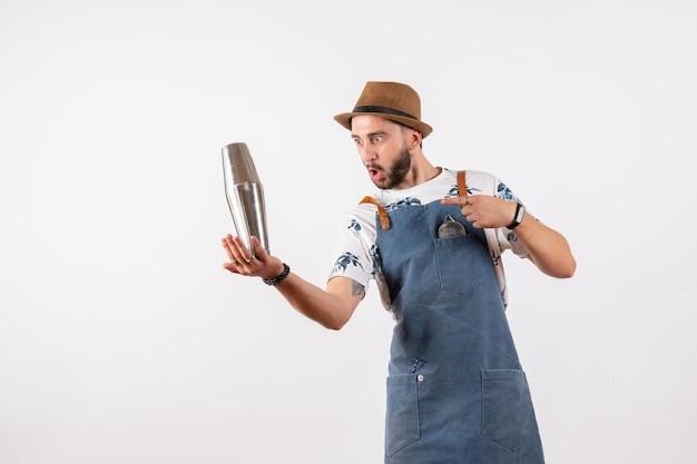 Vue de face barman masculin tenant un shaker d'argent sur un mur blanc bar à alcool club de nuit boissons modèle de travail