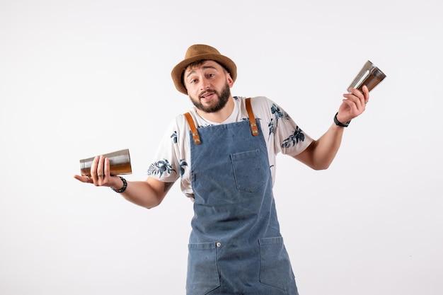 Vue de face barman masculin tenant un shaker sur un mur blanc club de nuit bar de nuit boisson alcoolisée couleur de travail