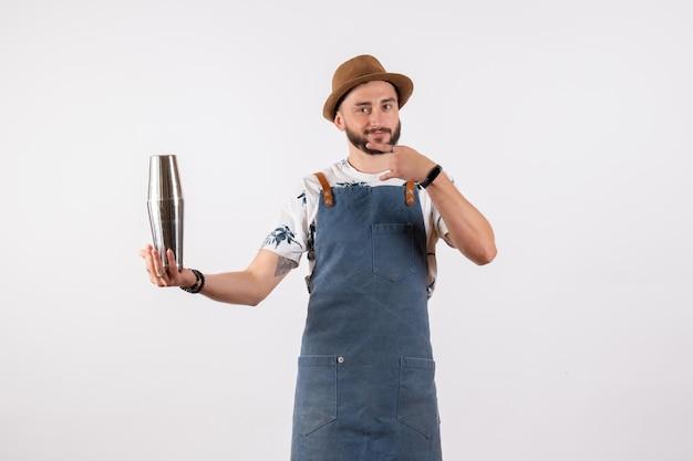 Vue de face barman masculin tenant un shaker sur un mur blanc club de nuit travail d'alcool bar boisson