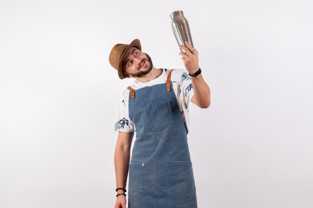 Vue de face barman masculin tenant un shaker sur un mur blanc club de travail de nuit boissons alcoolisées barre de couleur