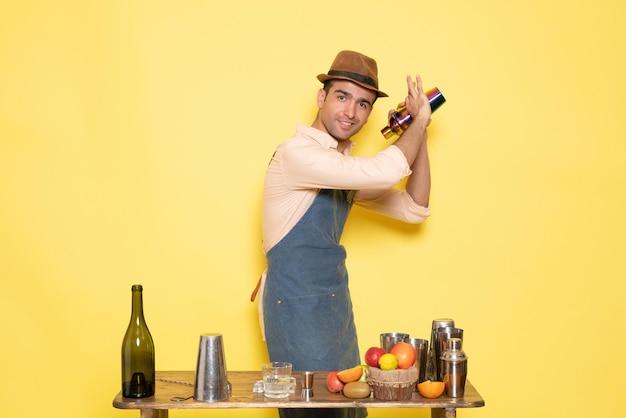 Vue de face barman masculin travaillant avec un shaker et faisant un verre sur un mur jaune la nuit boit de l'alcool bar club homme