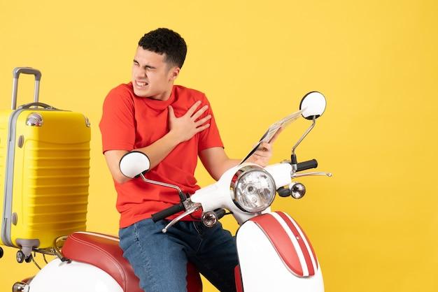 Vue de face beau jeune homme sur cyclomoteur tenant son cœur avec douleur