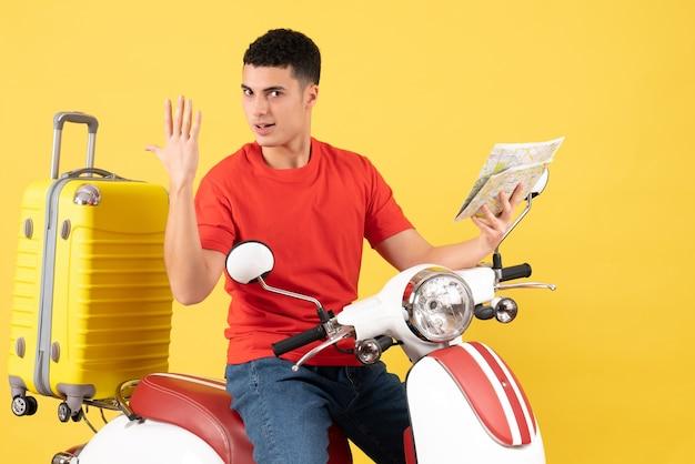 Vue de face beau jeune homme sur cyclomoteur avec valise tenant la carte