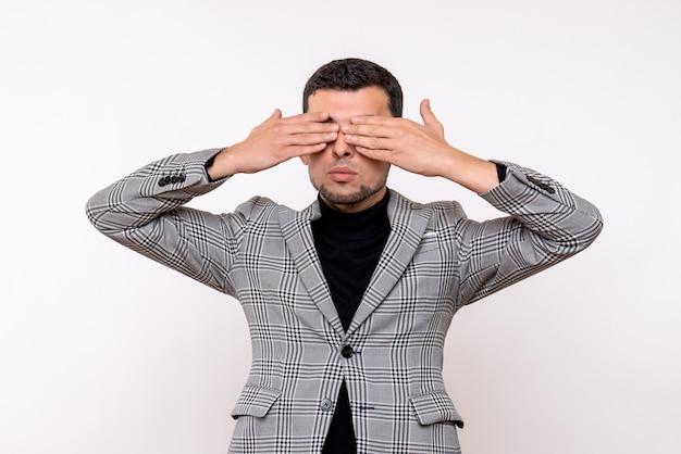 Vue de face beau mâle en costume couvrant ses yeux debout sur fond blanc