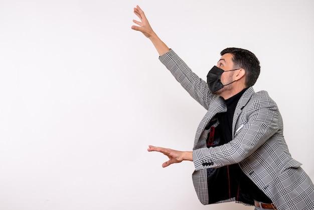 Vue de face beau mâle en costume essayant d'attraper quelque chose debout sur fond blanc