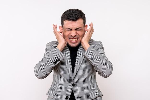 Vue de face beau mâle en costume fermant ses oreilles avec les doigts debout sur fond blanc
