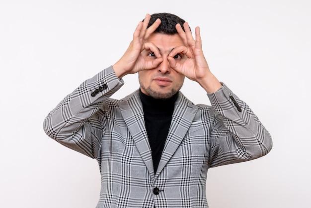 Vue de face beau mâle en costume mettant ok signe devant ses yeux debout sur fond blanc