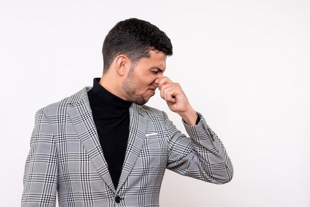 Vue de face beau mâle en costume tenant son nez debout sur fond blanc