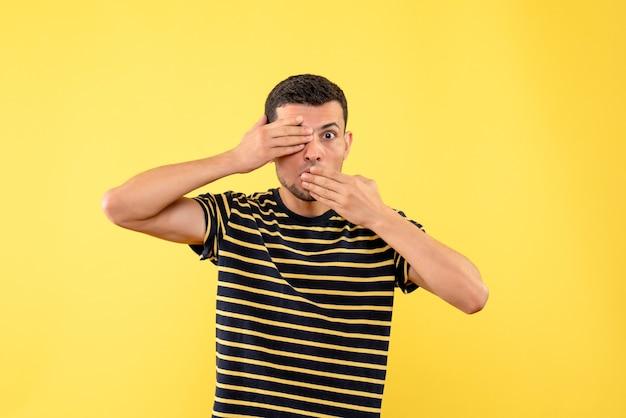 Vue de face beau mâle en t-shirt rayé noir et blanc couvrant la bouche et les yeux sur fond isolé jaune