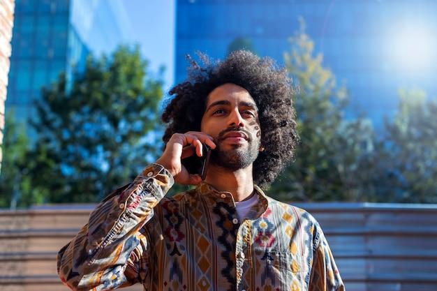 Vue de face d'un bel homme afro souriant à l'aide d'un téléphone portable tout en restant à l'extérieur