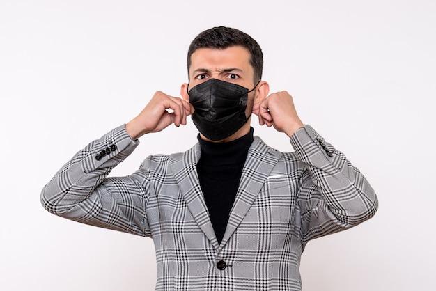 Vue de face bel homme au masque noir debout sur fond blanc isolé