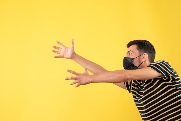 Vue de face bel homme au masque noir essayant d'atteindre quelque chose sur fond isolé jaune