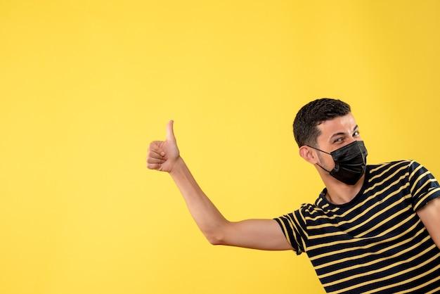 Vue de face bel homme au masque noir faisant le pouce vers le haut signe sur fond isolé jaune