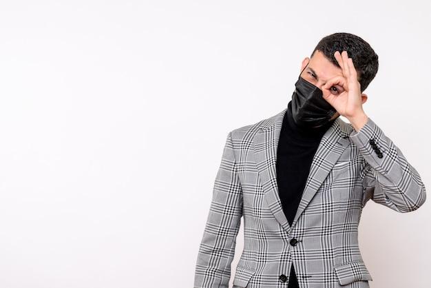 Vue de face bel homme en costume mettant okey signe devant son œil debout sur fond blanc isolé