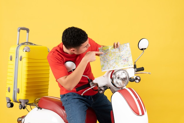 Vue de face bel homme sur cyclomoteur en regardant la carte