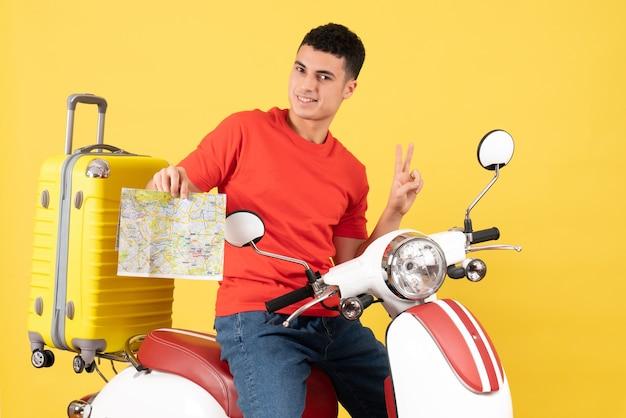Vue de face bel homme sur cyclomoteur tenant la carte faisant signe de la victoire