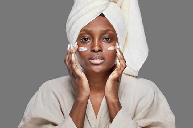 Vue de face sur une belle femme afro-américaine bénéficiant de soins de la peau et regardant la caméra avec une crème pour le visage ou une crème hydratante