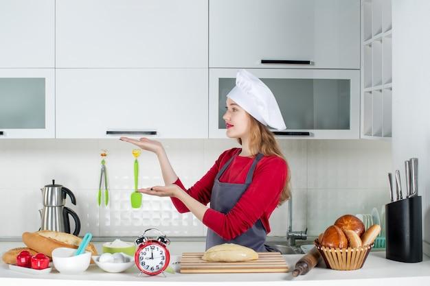 Vue de face belle femme en chapeau de cuisinier et tablier levant les mains dans la cuisine