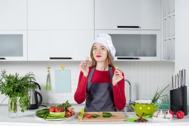 Vue de face belle femme chef en chapeau de cuisinier mettant des tranches de concombre sur son visage
